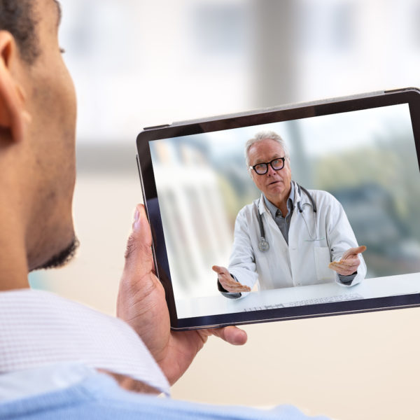 A Patient speaks with his doctor on a tablet computer